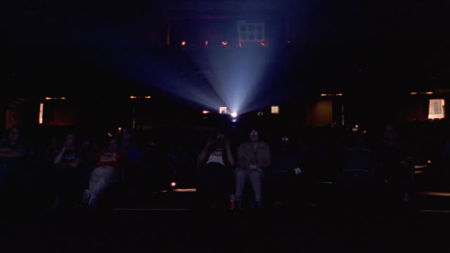 1991 time lapse wide shot people sitting in movie theater watching screen / Los Angeles