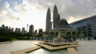 Time lapse wide shot people walking around Al-Asyikin mosque and fountain with Petronas Towers and Menara Kuala Lumpur Tower in background/ Kuala Lumpur