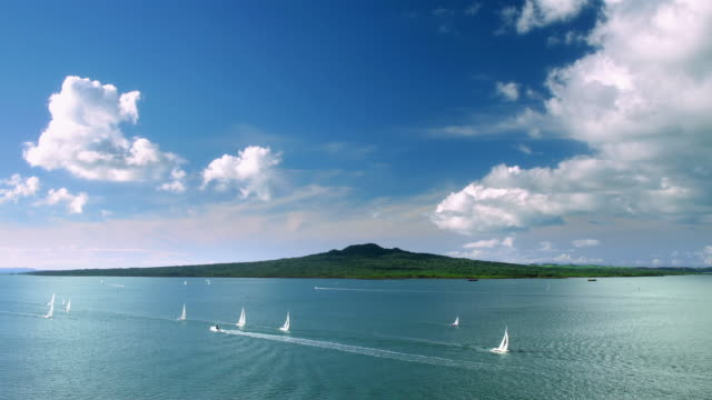 Time lapse wide shot yachts sailing in water off Auckland Harbor with Rangitoto Island / New Zealand