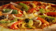 Time lapse zoom into vegetable pizza cooking / cheese melting and bubbling
