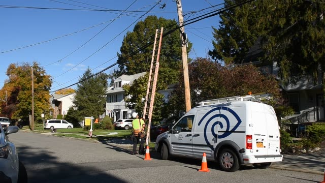 A Time Warner Cable Inc technician climbs a ladder to perform maintenance on one of the company's network poles in Leonia New Jersey US on Friday Oct...