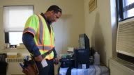 A Time Warner Cable Inc technician fixes a problem with the cable internet inside the home of a customer in Pallisades Park New Jersey US on Friday...
