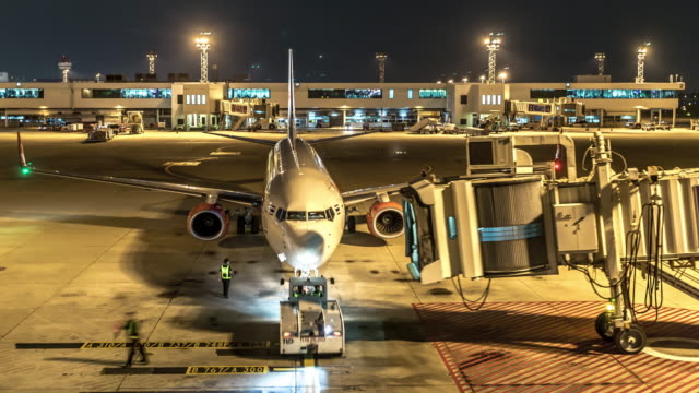 4K Time-Lapse: Arrival of Airplane to terminal Jetway Dock night