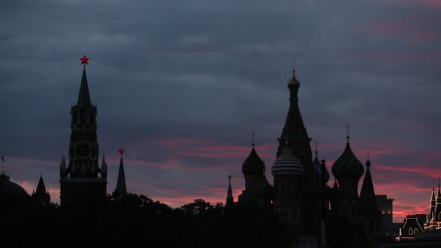 Timelapse at sunset of the Spasskaya tower and St Basil's cathedral standing silhouetted in Moscow Russia on Wednesday July 5 2017