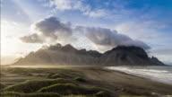 4 K Time-lapse: mooie zonsondergang zwarte zand strand in IJsland met enorme duinen en Atlantische Oceaan. Vestrahorn berg op de achtergrond.