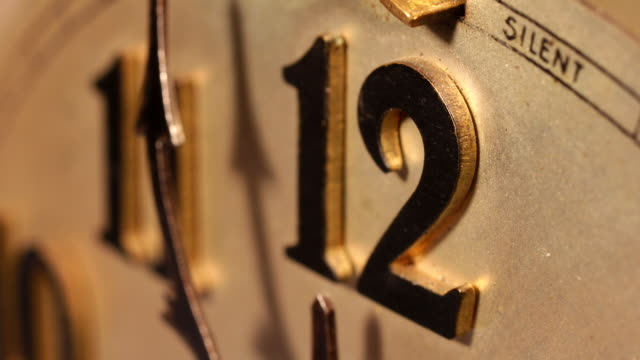Timelapse, close up of old clock hands passing over midnight