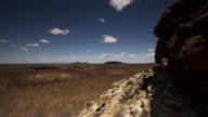 Timelapse clouds scud over plain towards cliffs.