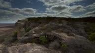 Timelapse clouds scud over rocky outcrop.