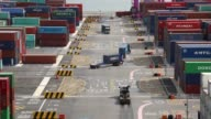 Timelapse container trucks drive past stacked shipping containers at the Sun Kwang Newport Container Terminal in Incheon New Port in Incheon South...