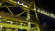 Timelapse cranes load containers from lorries onto ship at night, Jebel Ali, Dubai