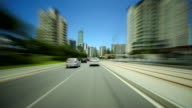 'Timelapse day blue skies with fluffy white clouds point of view from front of car driving through Gold Coast streets and traffic includes stopping...