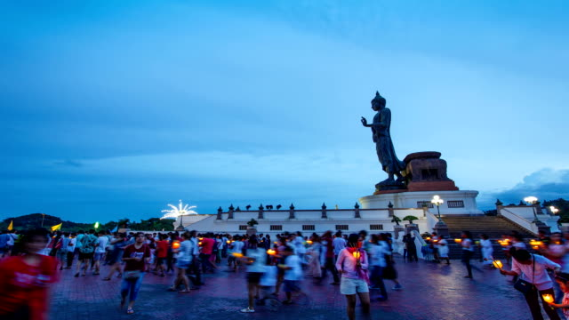 Time-lapse Day to Night Asalha Puja Day, Buddhists holding lit candle and walk