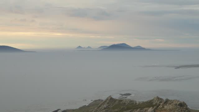 Timelapse dusk falls over misty sea and islands, Falkland Islands