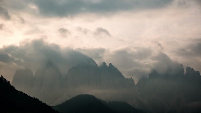 Timelapse Fog rolls across flowing over mountains