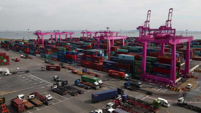 Timelapse gantry cranes move among stacked shipping containers as container trucks drive past at the Sun Kwang Newport Container Terminal in Incheon...