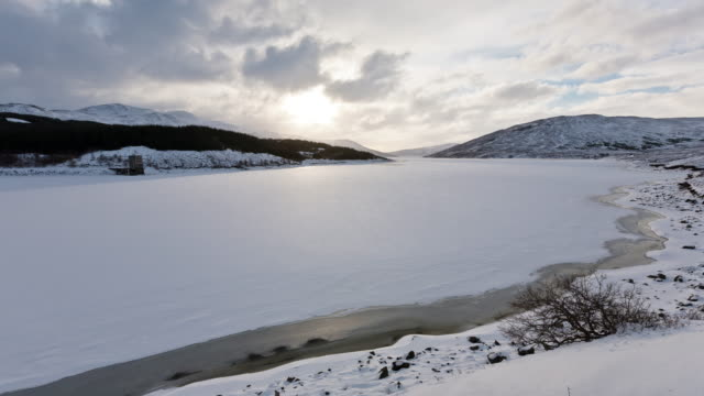 Time-lapse of a frozen lake in Scotland with the cloud and sun-rise reflecting off the snow and ice
