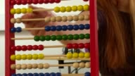 timelapse of abacus beads being counted by woman