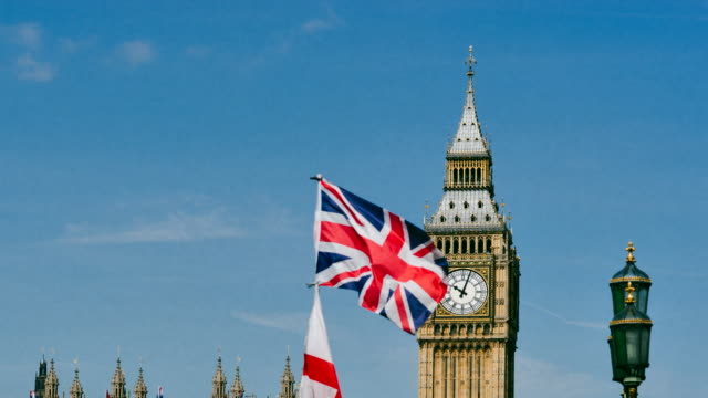 Time-lapse of Big Ben with flags against blue sky