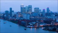 Time-lapse of Canary Wharf from Rotherhithe shot across the river thames in London sky turns from twilight to night with boat traffic