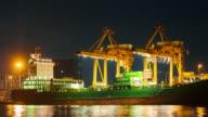 Timelapse of cargo ship loading goods at shipping port,Tilt shot