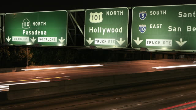 timelapse of cars under Hollywood freeway sign