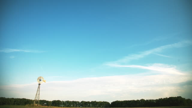 Timelapse of clouds over a windmill, beautiful blue sky