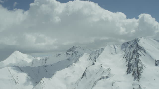 Timelapse of clouds over high mountains.
