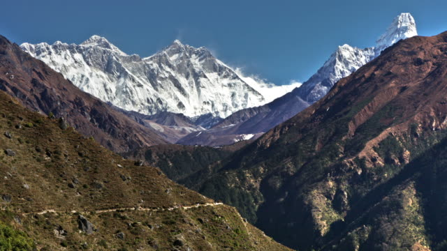 Time-lapse of Everest and surrounding peaks and people on a foreground trail.
