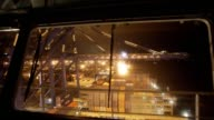 Timelapse of gantry cranes loading shipping containers onto CMA CGM SA's Benjamin Franklin container ship viewed from a window on the bridge while...