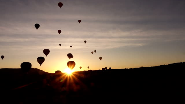 timelapse of hot air balloons in the air from within the valley in Cappadocia