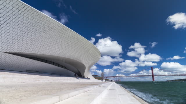 Timelapse of MAAT museum of Lisbon with the 25th of April Bridge over the Tagus river. Portugal. April, 2017