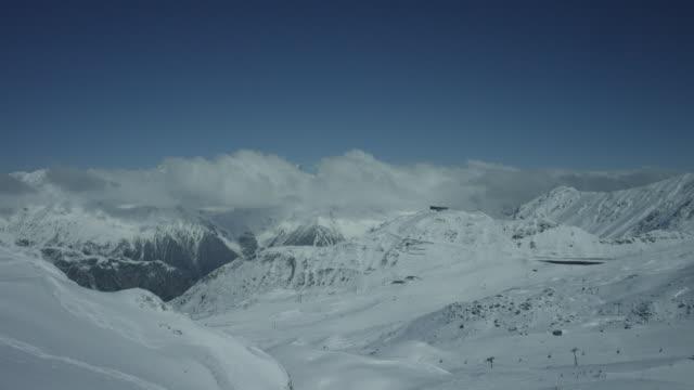 Timelapse of mountain panorama and ski lift on a mountain summit.