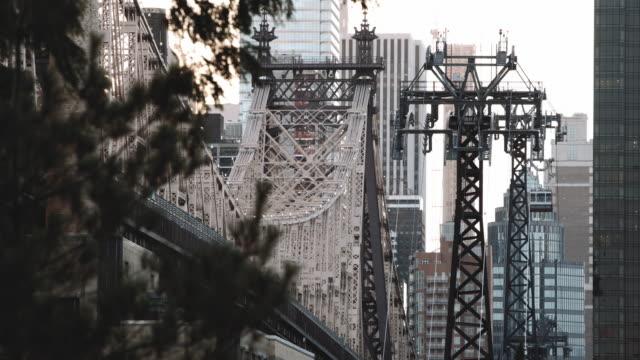 Timelapse of NYC's Roosevelt Island Tram passing alongside The Queensboro Bridge - 4k