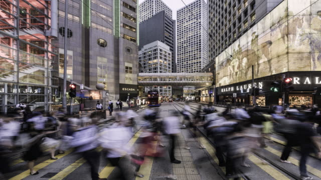 timelapse of people crossing street in financial district