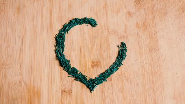 Timelapse of Spirulina Algae Flakes Making a Heart