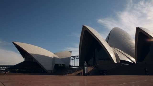 Timelapse of visitors as the Sydney Opera House stands against a blue sky and passing clouds in Sydney Australia on Friday July 3 2015
