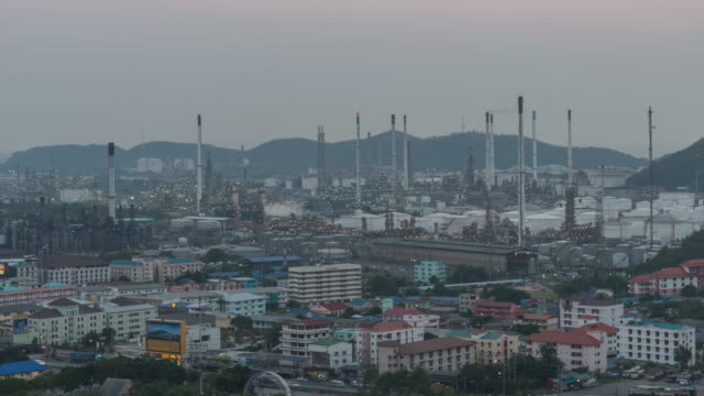4K Time-lapse: Oil refinery plant petrochemical industry and transport at sunset time, zoom out