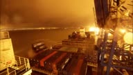 Timelapse on board CMA CGM SA's Benjamin Franklin container ship as night turns to day and gantry cranes load shipping containers in the rain upon...