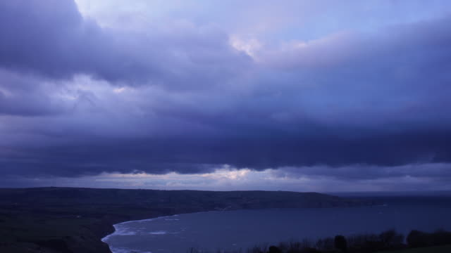 Timelapse, pan over Robin Hoods Bay as simulated lightning brighten the dark storm clouds gathering in the blackened sky