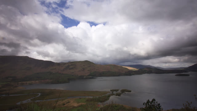 Timelapse rain falls from clouds over hills and lake, Lake District, UK