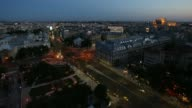 A timelapse sequence filmed at dusk shows high angle view traffic with illuminated headlights driving around the University roundabout in the center...