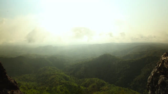 Timelapse sun burns away mist over rainforest, Megatha, Myanmar