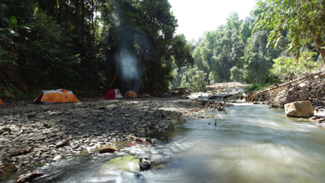 Timelapse sun drifts over river and rainforest camp, Gwa, Myanmar