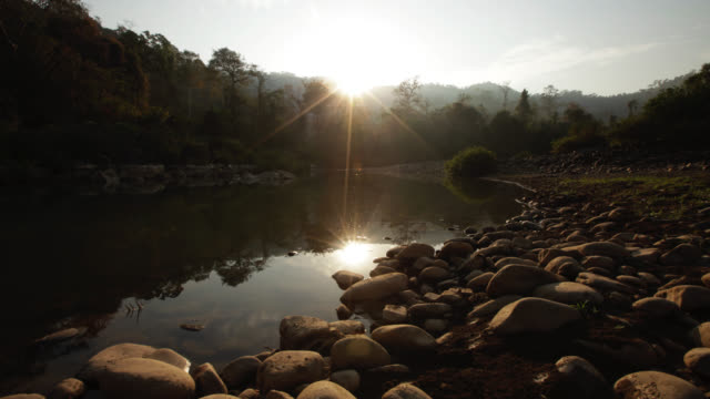 Timelapse sun rises over rainforest and river, Salu, Myanmar