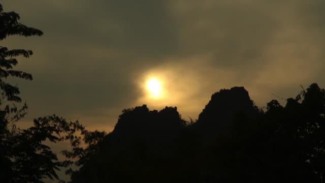 Timelapse sun rises over rainforested hills, Megatha, Myanmar