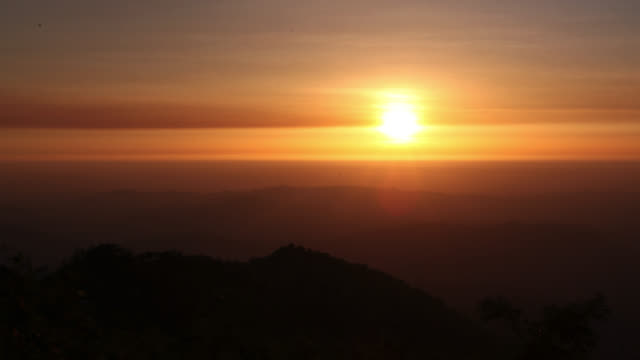 Timelapse sun sets over rainforested hills, Salu, Myanmar