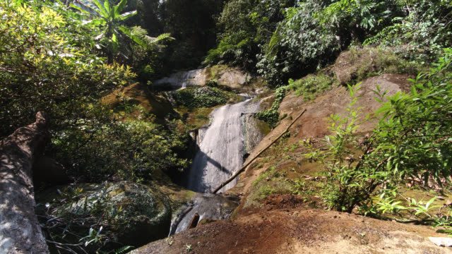Timelapse sunlight and shadows shift over rainforest waterfall, Htamanthi, Myanmar