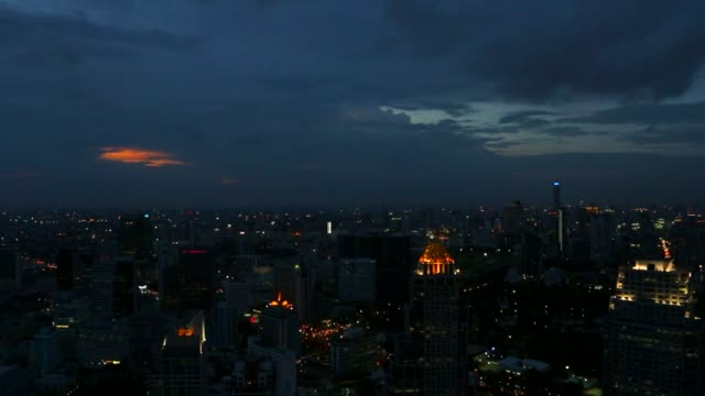 Timelapse sunset and gradual illumination of moving traffic and buildings as day turns to night in Bangkok Thailand on Friday July 18 2014