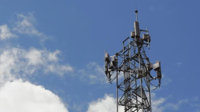 Zeitraffer: Fernmeldeturm mit blauem Himmel und Wolken