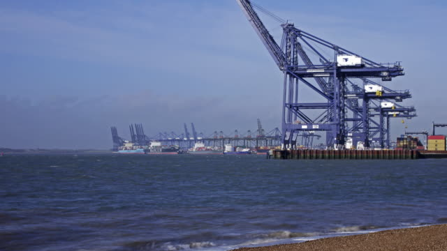Timelapse tilt up and zoom in to cranes and container ships in the docks at the Port of Felixstowe